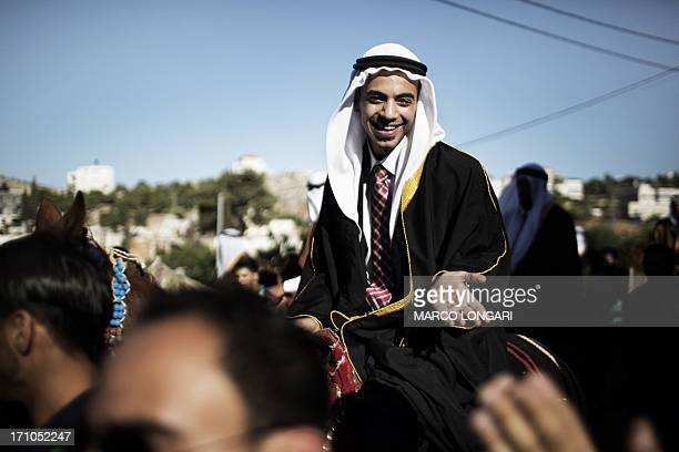 A Palestinian groom smiles while riding a horse during a mass wedding in the West Bank village of Silwad on June 21 2013 A total of 22 Palestinian...