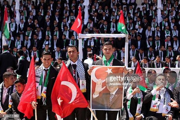 Palestinian grooms hold a poster of Turkish President Recep Tayyip Erdogan and Turkish national flags during a mass wedding ceremony at the Yarmouk...