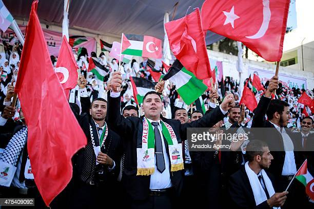 Palestinian grooms wave Palestinian and Turkish national flags during a mass wedding ceremony at the Yarmouk Stadium in Gaza on May 31 2015 Two...
