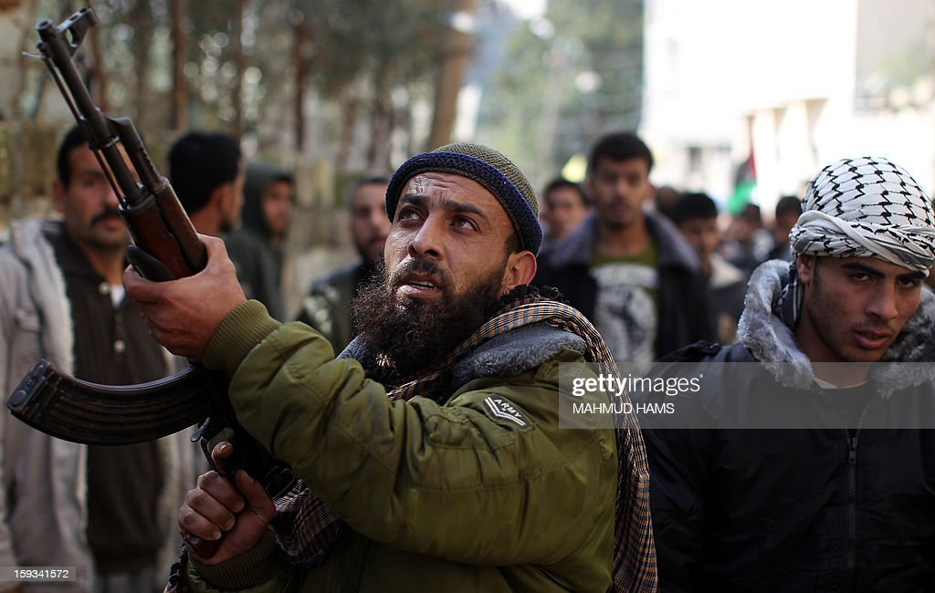 A Palestinian gunman fires shots in the air during the funeral of Anwar Mohammed al-Mamluk in Gaza City on January 12, 2013. Israeli soldiers shot dead Mamluk and wounded another in the northern Gaza Strip, a spokesman for the territory's emergency services said.