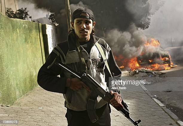 A palestinian gunman stands next to burning vehicles belonging to the local electricity company on December 20 2006 in Gaza city Gaza Strip The...