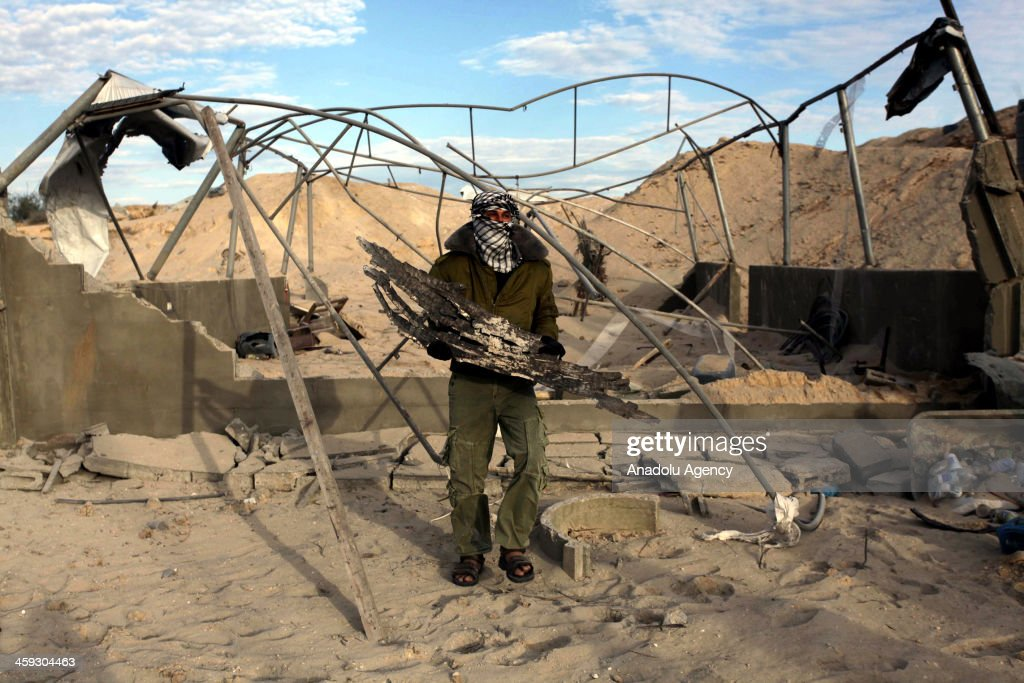 Palestinian Hamas members inspect Hamas training camp on December 25, 2013 after it was hit by an Israeli air strike on Tuesday, in Dir al-Balah region of Gaza Strip.