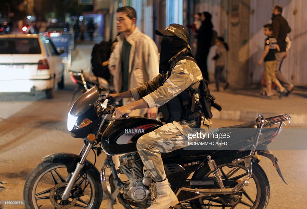 A Palestinian Hamas militant drives his motorcycle during a rally in support with Palestinian prisoners jailed in Israeli prisons on April 18, 2013. Israeli President Shimon Peres pardoned on April 13 a Palestinian prisoner who had carried out two long-term hunger strikes, citing concerns over his health, a statement from his office said. AFP PHOTO/MOHAMMED ABED