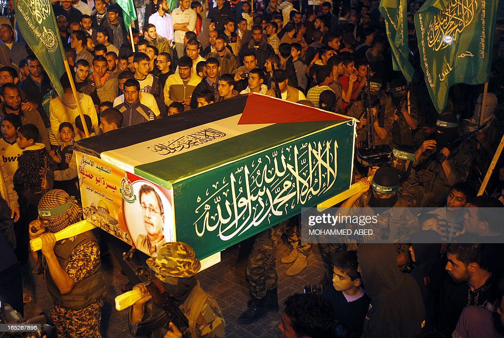 Palestinian Hamas militants hold a symbolic coffin of Maisara Abu Hamdiyeh, an Israeli-held prisoner who died of cancer while in detention, during a protest against his death in the Jabalia reffuge camp in the northern Gaza Strip on April 2, 2013. The Palestinian leadership blamed Israel for the death of the long-term prisoner with cancer, hiking tensions over a tinderbox issue closely followed on the Palestinian street.