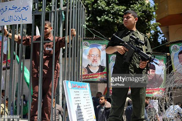 Palestinian Hamas militants stand guard during a rally marking Palestinian Prisoner Day in Gaza City April 17 2016 The sign reads quotThe enemy will...