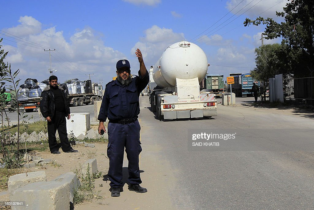 A Palestinian Hamas policeman gestures to arriving trucks carrying supplies as they cross into Rafah town through the Kerem Shalom crossing between Israel and the southern Gaza Strip on March 5, 2013. Israel reopened the Kerem Shalom commercial crossing into southern Gaza, six days after closing it after a rocket fired from the Palestinian enclave hit the Jewish state.
