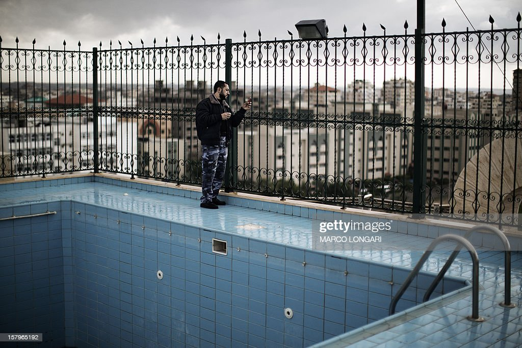 A Palestinian Hamas policeman takes pictures with his phone on the rooftop of a building overlooking a rally to mark the 25th anniversary of Hamas in Gaza City on December 8, 2012. More than 100,000 Palestinians gathered in Gaza for the rally to celebrate the occasion which will be addressed by the ruling Islamist movement's leader in exile Khaled Meshaal, who is on his first ever visit to Gaza.
