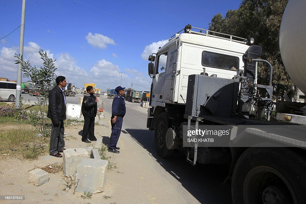 Palestinian Hamas policemen inspect trucks carrying supplies as they cross into Rafah town through the Kerem Shalom crossing between Israel and the southern Gaza Strip on March 5, 2013. Israel reopened the Kerem Shalom commercial crossing into southern Gaza, six days after closing it after a rocket fired from the Palestinian enclave hit the Jewish state.