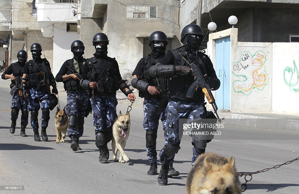 Palestinian Hamas policmen march with their police dogs along a street in Gaza City on April 24, 2013. After prime minister Salam Fayyad resigned earlier in April, Palestinian politicians immediately called for elections and a national unity government to reconcile bitter rivals Fatah and Hamas. AFP PHOTO/MOHAMMED ABED