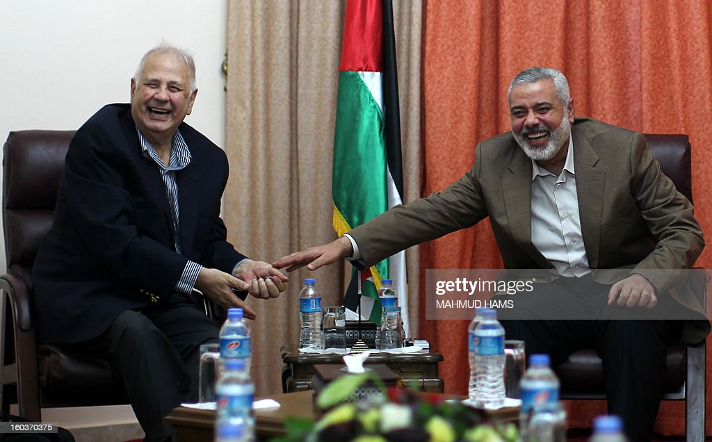 Palestinian Hamas prime minister Ismail Haniya (R) shares a laugh with Central Elections Commission chief Hanna Nasser during a meeting in Gaza City on January 30, 2013. Gaza's Hamas rulers authorised the Palestinian elections commission to begin voter registration as part of efforts to restart reconciliation, an official said. AFP PHOTO / MAHMUD HAMS