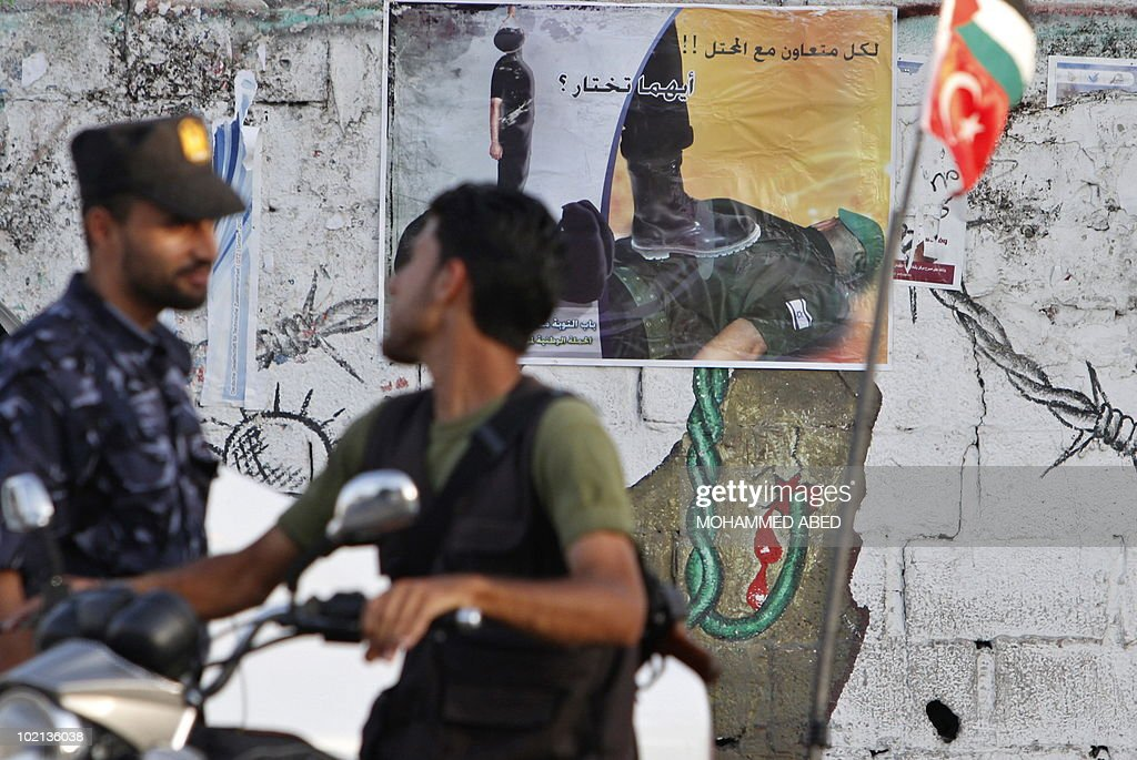 Palestinian Hamas security men chat near a poster and mural warning informers to stop spying for Israel on June 15, 2010 in Gaza City.