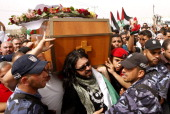 Palestinian Hamas security personnel and foreigners carry the coffin of Italian activist Vittorio Arrigoni during a 'state funeral' in Gaza City on...