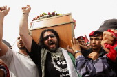 Palestinian Hamas security personnel and foreigners carry the coffin of Italian activist Vittorio Arrigoni during a 'state funeral' in Rafah southern...