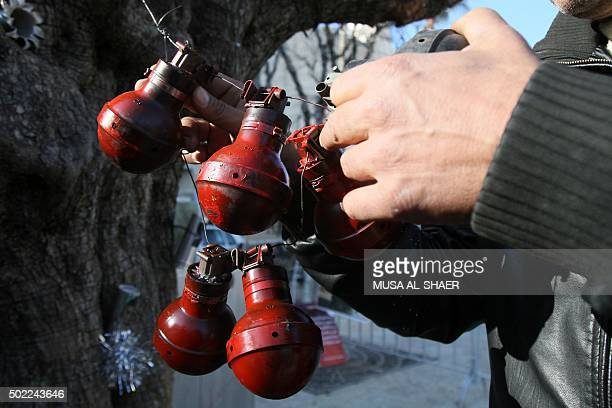 A Palestinian hangs used tear gas canisters as Christmas decorations on the Manger Square near the Church of the Nativity where Christians believe...