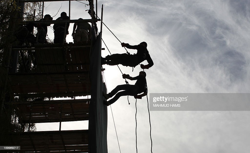 Palestinian high-school students show off their skills during a graduation ceremony from a military school course organised by the Hamas security forces and the Hamas Minister of Education on January 24, 2013 in Gaza City. AFP PHOTO/MAHMUD HAMS