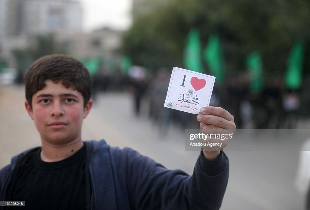 A Palestinian hold a placard, written 'I love Prophet Mohammad' during a demonstration, organized by Hamas youths, against the printing of satirical cartoons of Muslim's Prophet Mohammad by French magazine Charlie Hebdo, in Gaza City, Gaza on January 26, 2015.