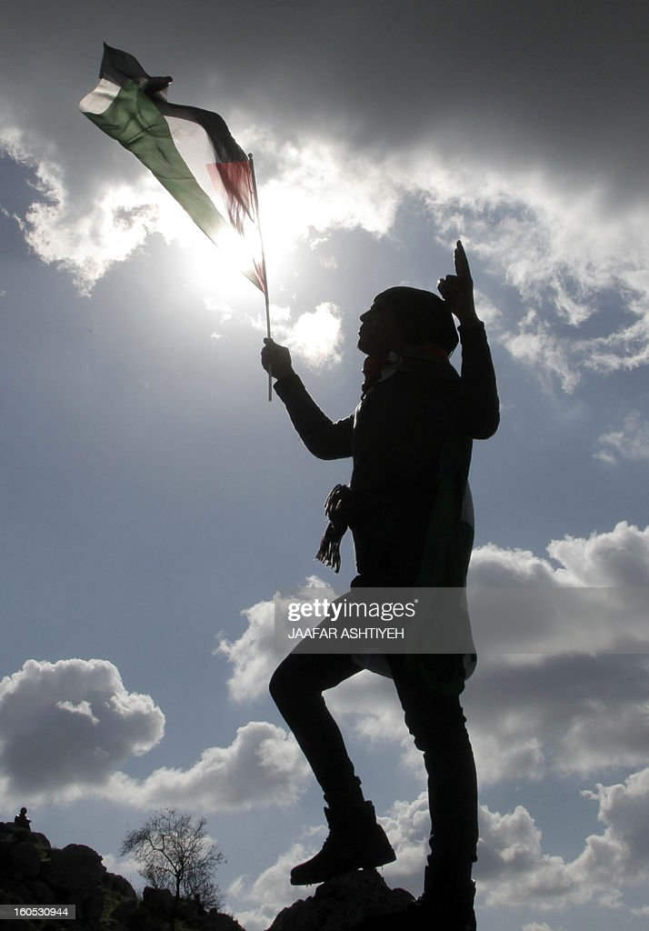 A Palestinian holds a flag on the top of a hill as demontrators set up a new camp to protest against Jewish settlements near the West Bank village of Burin on February 2, 2013. An AFP correspondent said the Israeli army used tear gas and violence to remove hundreds of people who had set up four temporary huts and three tents near Burin, south of Nablus in the occupied West Bank, in a third attempt at the novel form of protest against Jewish settlements. AFP PHOTO /JAAFAR ASHTIYEH