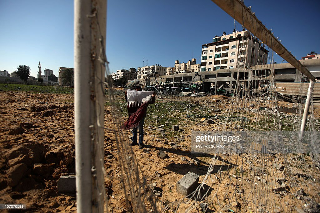 A Palestinian holds the flag of Qatar found in the rubble of the bombed Palestine Stadium in Gaza City on November 28, 2012. The stadium was bombed by the Israeli airforce during a conflict between the ruling Hamas party and the Israeli military between 14 and 21 November 2012.