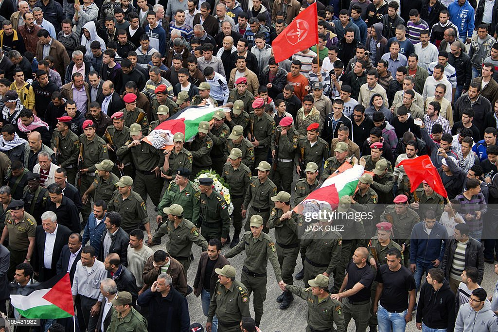 Palestinian honour guards carry the bodies of Amer Nasser and Naji Balbisi, two teenagers shot by Israeli troops, during their funeral in the West Bank town of Anabta near Tulkarem on April 4, 2013. The West Bank simmered with anger as thousands joined the funeral of prisoner Maisara Abu Hamdiyeh who died in an Israeli jail and similar numbers gathered to bury two teens shot dead overnight during clashes over the death of the prisoner, Israeli and Palestinian sources said.