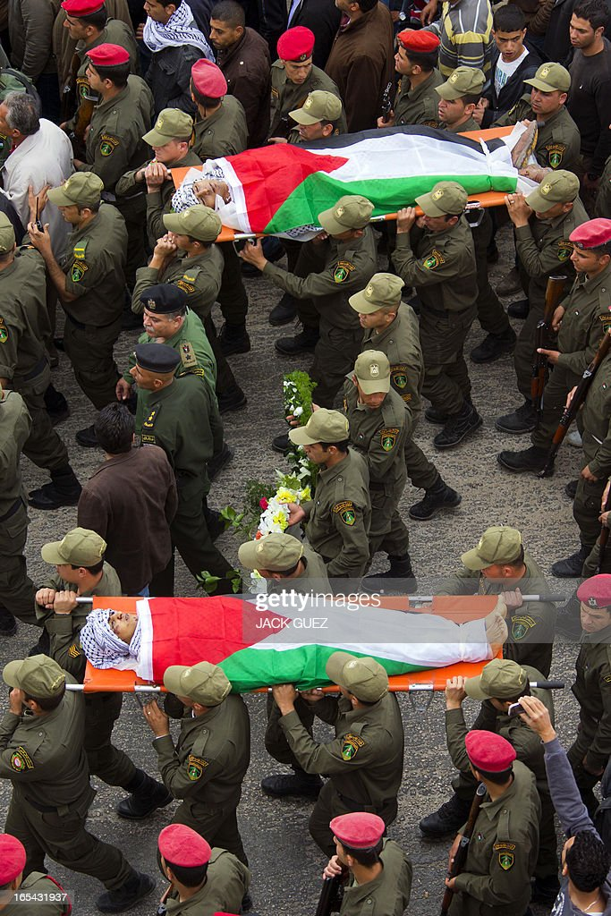 Palestinian honour guards carry the bodies of Amer Nasser and Naji Balbisi, two teenagers shot by Israeli troops, during their funeral in the West Bank town of Anabta near Tulkarem on April 4, 2013. The West Bank simmered with anger as thousands joined the funeral of prisoner Maisara Abu Hamdiyeh who died in an Israeli jail and similar numbers gathered to bury two teens shot dead overnight during clashes over the death of the prisoner, Israeli and Palestinian sources said. AFP PHOTO / JACK GUEZ
