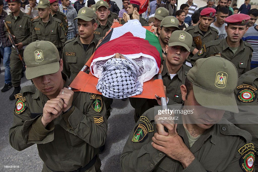 Palestinian honour guards carry the body of a Palestinian teenager shot by Israeli troops during a funeral in the West Bank town of Anabta near Tulkarem on April 4, 2013. The West Bank simmered with anger as thousands joined the funeral of prisoner Maisara Abu Hamdiyeh who died in an Israeli jail and similar numbers gathered to bury two teens shot dead overnight during clashes over the death of the prisoner, Israeli and Palestinian sources said. AFP PHOTO / JACK GUEZ