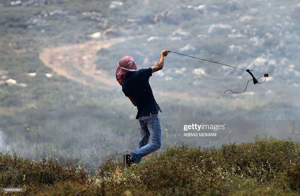 A Palestinian hurls rocks at Israeli security forces during clashes following a protest against the confiscation of Palestinian land by Israel in the West Bank from Deir Jarir east of Ramallah, on May 17, 2013.