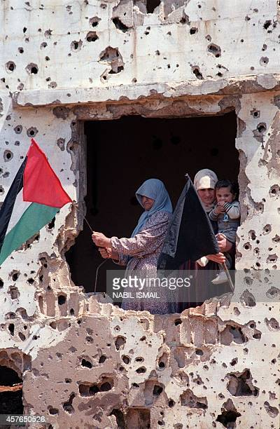 Palestinian inhabitants of Shatila refugee camp near Beirut place 18 April 1988 a Palestinian flag and a black flag as a sign of mourning after PLO...