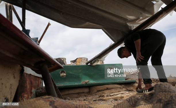 A Palestinian inspects damage incurred to a Hamas post that was hit by Israeli tank and aircraft fire the previous night east of the southern Gaza...