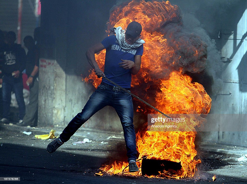 A Palestinian is affected by the fire during clashes with Israeli soldiers following the funeral of Anas al-Atrash, after he was killed by Israeli soldiers on November 7, 2013 in North Jerusalem. November 8, 2103, Hebron, West Bank.