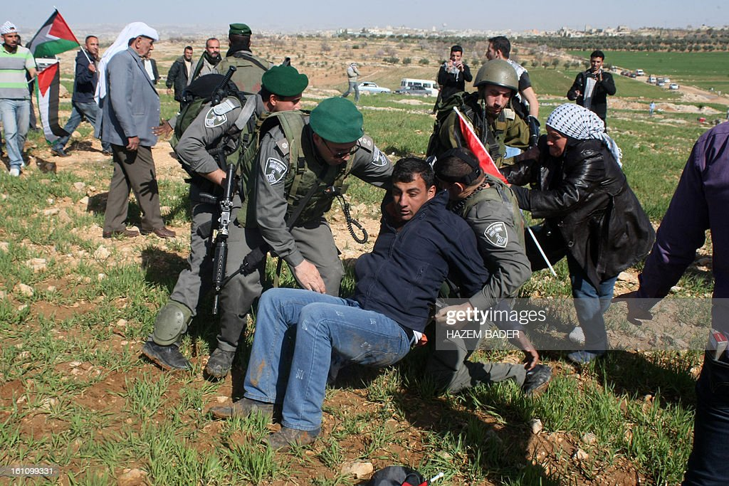A Palestinian is arrested by an Israeli soldier as Palestinian activists tried to set up a new encampment to protest against settlement building in the Yatta, south of the West Bank city of Hebron on February 9, 2013. Soldiers dismantled tents that were being erected in two different areas near the town of Yatta, and forced activists to leave, the Palestinian witnesses said. BADER