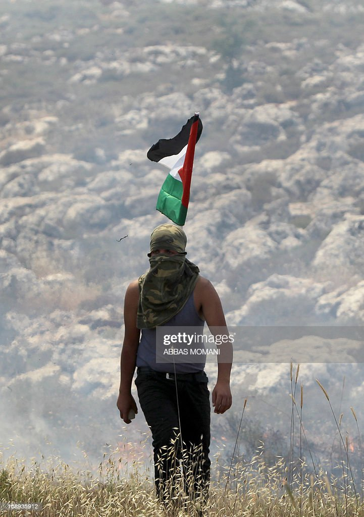 A Palestinian is pictured during clashes with Israeli security forces following a protest against the confiscation of Palestinian land by Israel in the West Bank from Deir Jarir east of Ramallah, on May 17, 2013.