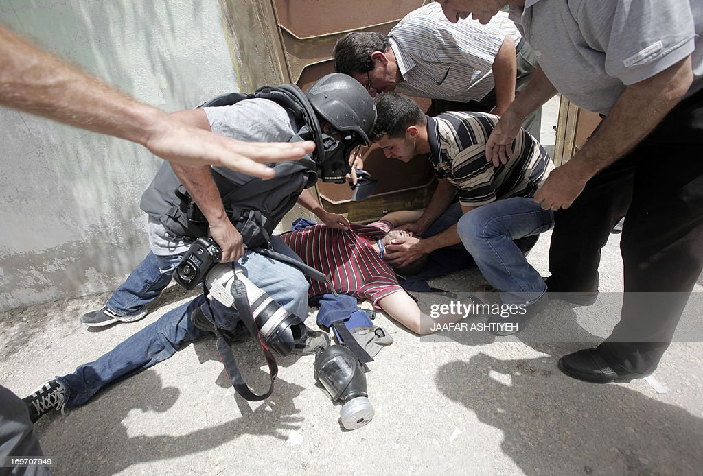A Palestinian journalist, Ashraf Abu Shaweesh is given assistance after being injured by tear gas during clashes following a protest against the expropriation of Palestinian land by Israel on May 31, 2013 in the village of Kfar Qaddum, near the occupied West Bank city of Nablus.