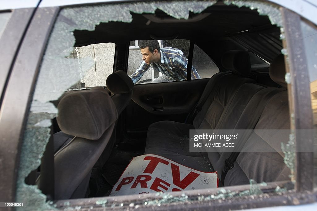 A Palestinian journalist inspects his work car in Gaza City on November 18, 2012. An Israeli air strike hit a Gaza City media building on November 18, injuring at least six journalists, as a separate raid in northern Gaza killed two people, Palestinian medical sources said. AFP PHOTO/MOHAMMED ABED