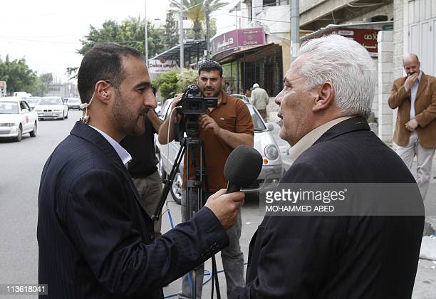 A Palestinian journalist working with the the Palestinian National Authority makes a interview in a Gaza City on May 4 2011 as his media crew is...