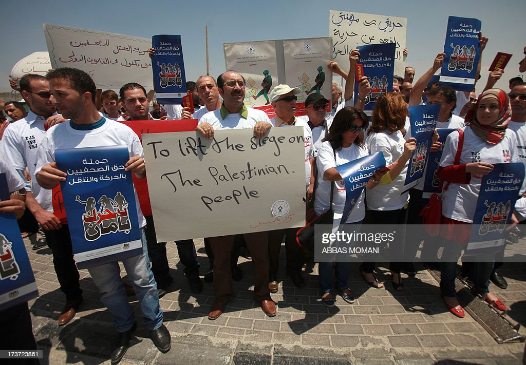 Palestinian journalists hold banners during a demonstration demanding for the free movement of journalists and Palestinians at the Qalandia checkpoint between Ramallah and Jerusalem, in the occupied West Bank on July 17, 2013.