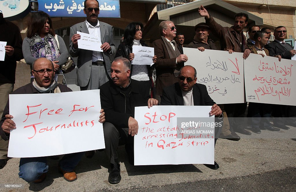 Palestinian journalists hold placards during a demonstration in support with reporters detained by Hamas in Gaza and to ask for their immediate release on January 27, 2013 in the West Bank city of Ramallah.