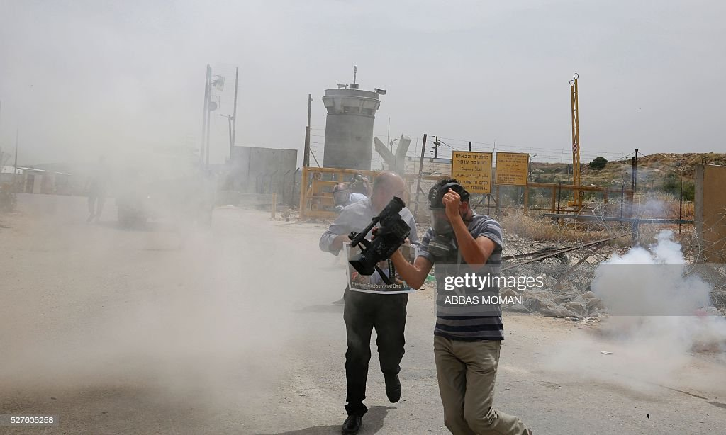 Palestinian journalists run for cover from tear gas canisters fired by Israeli forces during a demonstration in support of Palestinian journalists on the occasion of the World Press Freedom day outside the compound of the Israeli-run Ofer prison near Betunia in the occupied West Bank, on May 3, 2016 / AFP / ABBAS