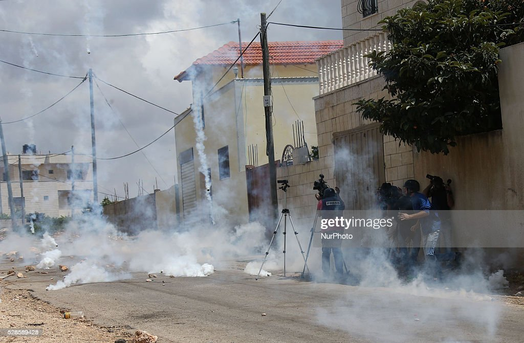 Palestinian Journalists take shelter from tear gas fired by Israeli soldier during a protest against the expanding of Jewish settlements in Kufer Qaddom village, near the West Bank city of Nablus. May 6, 2016.