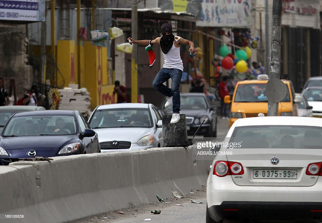 A Palestinian jumps between cars holding stones during clashes with Israeli soldiers following a rally commemorating the 37th anniversary of 'Land Day', on March 30, 2013 near the Qalandia checkpoint in the Israeli occupied West Bank. Nearly 200 Palestinians clashed with Israeli forces in Qalandia, who responded with tear gas.