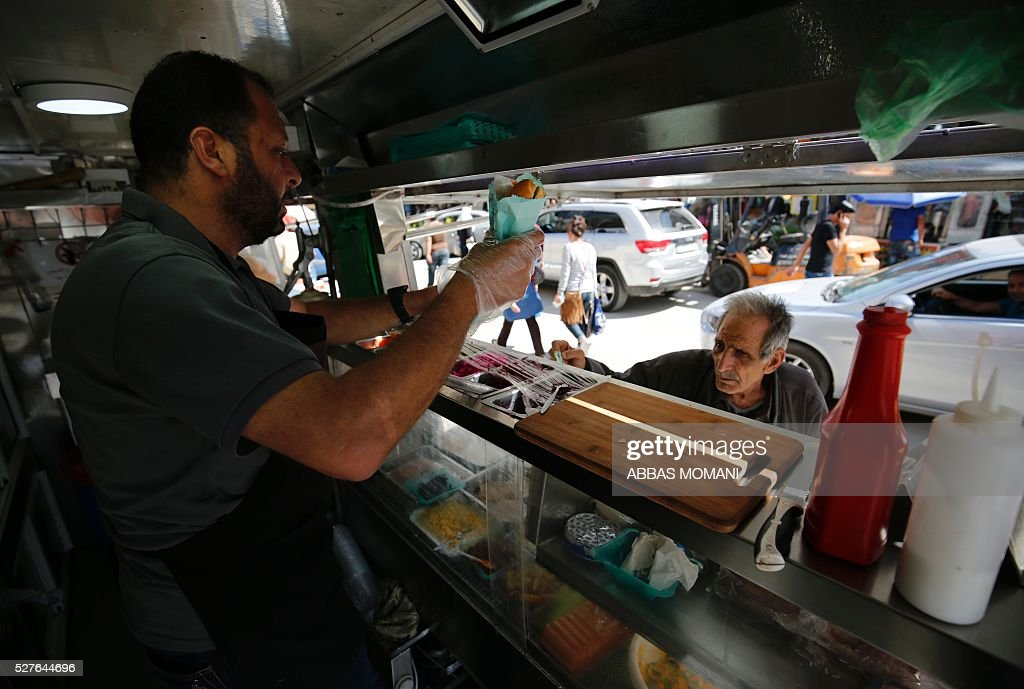 Palestinian Khaldun serves food to a customer at his food truck called 'Food Train' which he runs with his friend Abderrahman in the West Bank city of Ramallah on May 3, 2016. The idea for the first food truck authorised to operate in the Palestinian territories was born in an Israeli prison, where Khaldun al-Barghuthi and Abderrahman al-Bibi served food to their fellow inmates. EZZEDINE