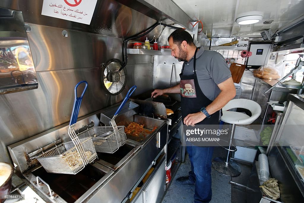 Palestinian Khaldun serves food to customers at his food truck called 'Food Train' which he runs with his friend Abderrahman in the West Bank city of Ramallah on May 3, 2016. The idea for the first food truck authorised to operate in the Palestinian territories was born in an Israeli prison, where Khaldun al-Barghuthi and Abderrahman al-Bibi served food to their fellow inmates. EZZEDINE