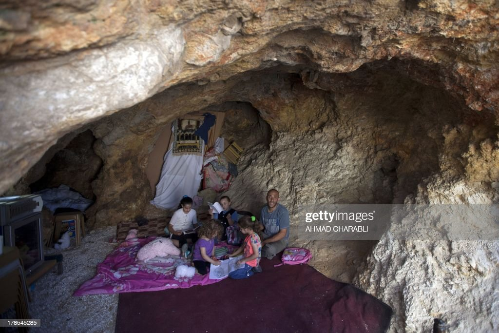 DAVISON - Palestinian Khaled Zir al-Husseini and his children sit on a matress on the floor of the cave that hosts the family since the demolition of their house by Israeli forces on August 29, 2013 in the east Jerusalem neighborhood of Silwan. Israeli forces have destroyed the homes of 716 Palestinians in 2013, according to HRW, which has recorded a three-fold increase in the number of demolitions in east Jerusalem since last year. AFP PHOTO/AHMAD GHARABLI