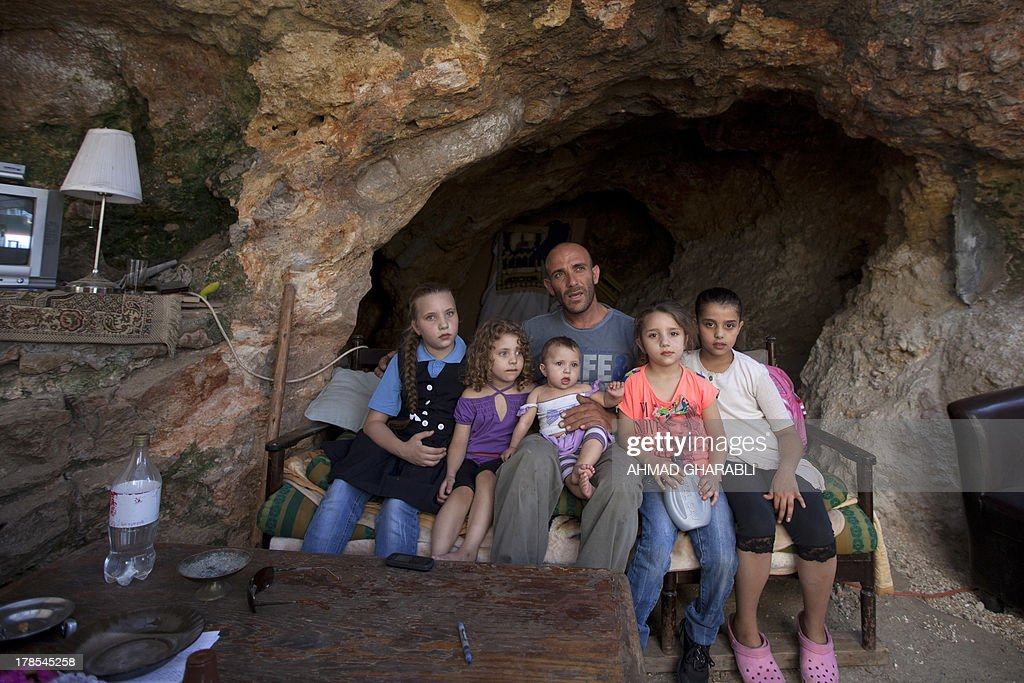 DAVISON - Palestinian Khaled Zir al-Husseini and his children sit on a sofa in the cave that hosts the family since the demolition of their house by Israeli forces on August 29, 2013 in the east Jerusalem neighborhood of Silwan. Israeli forces have destroyed the homes of 716 Palestinians in 2013, according to HRW, which has recorded a three-fold increase in the number of demolitions in east Jerusalem since last year.