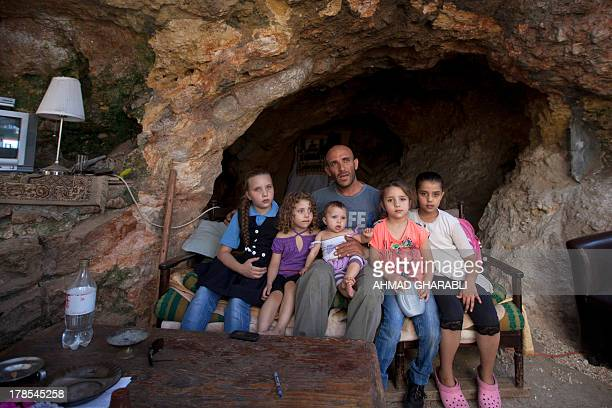 DAVISON Palestinian Khaled Zir alHusseini and his children sit on a sofa in the cave that hosts the family since the demolition of their house by...