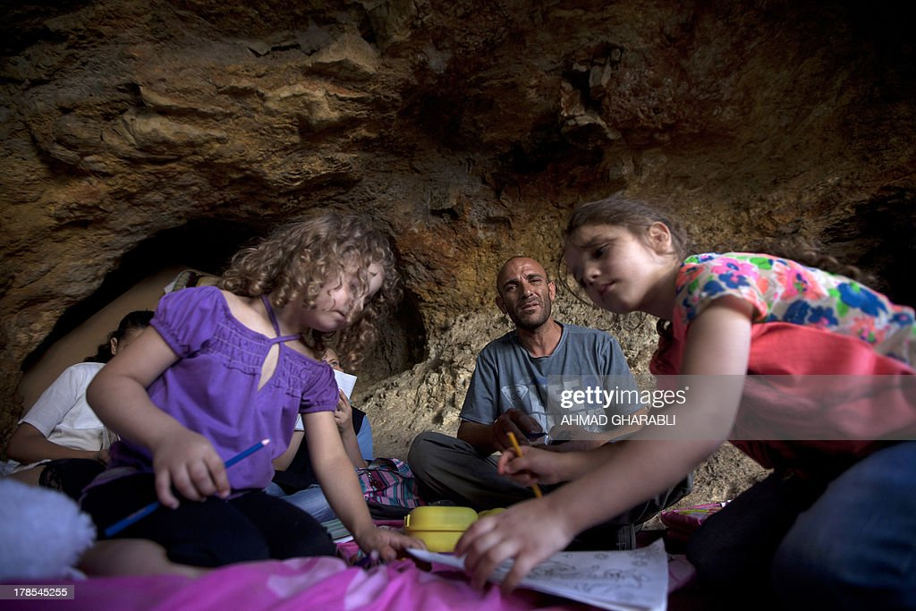 DAVISON - Palestinian Khaled Zir al-Husseini and his children sit on the floor of the cave that hosts the family since the demolition of their house by Israeli forces on August 29, 2013 in the east Jerusalem neighborhood of Silwan. Israeli forces have destroyed the homes of 716 Palestinians in 2013, according to HRW, which has recorded a three-fold increase in the number of demolitions in east Jerusalem since last year.