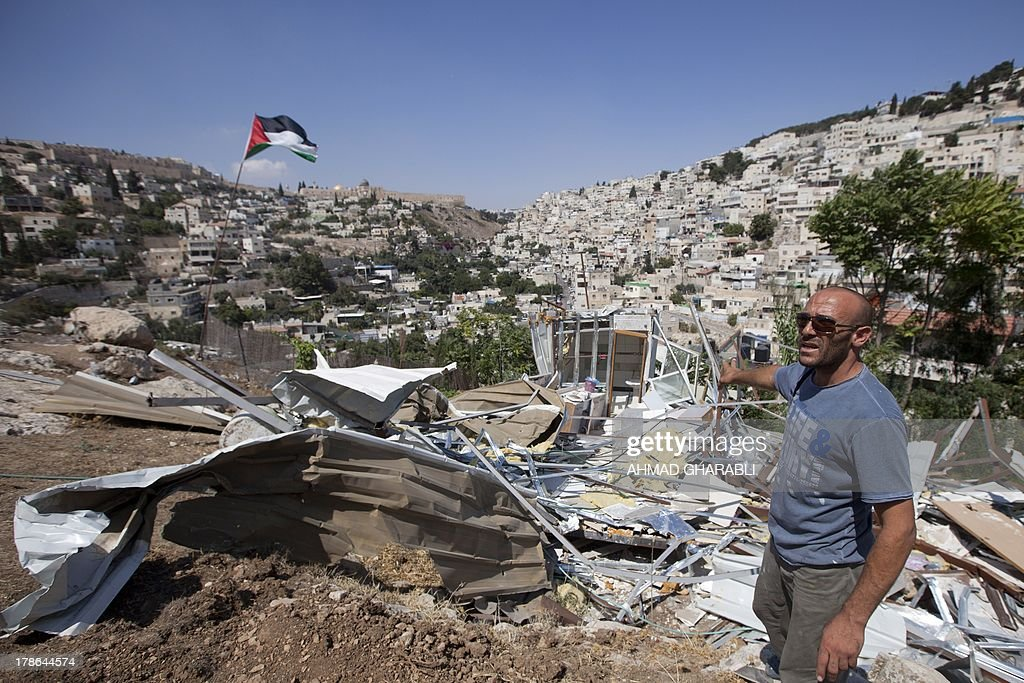 DAVISON - Palestinian Khaled Zir al-Husseini shows the remains of his house after its detruction by Israeli forces on August 29, 2013 in the east Jerusalem neighborhood of Silwan. Khaled Zir al-Husseini and his family moved into a cave down the hill, as they had to find a new roof. Israeli forces have destroyed the homes of 716 Palestinians in 2013, according to HRW, which has recorded a three-fold increase in the number of demolitions in east Jerusalem since last year.