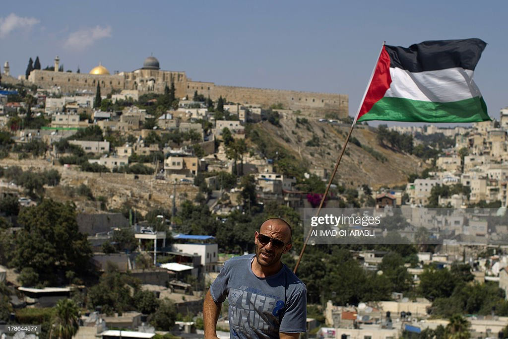 DAVISON - Palestinian Khaled Zir al-Husseini stands in front of a Palestinian flag on August 29, 2013 in the east Jerusalem neighborhood of Silwan. Khaled Zir al-Husseini and his family moved into a cave down the hill, as they had to find a new roof following the destruction of their house by Israeli forces. Israeli forces have destroyed the homes of 716 Palestinians in 2013, according to HRW, which has recorded a three-fold increase in the number of demolitions in east Jerusalem since last year.