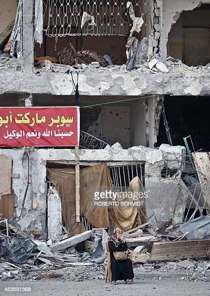 Palestinian Khitam Moussa sits on a chair outside an apartment building on August 14 2014 in Beit Hanun northern Gaza Strip which was heavily damaged...