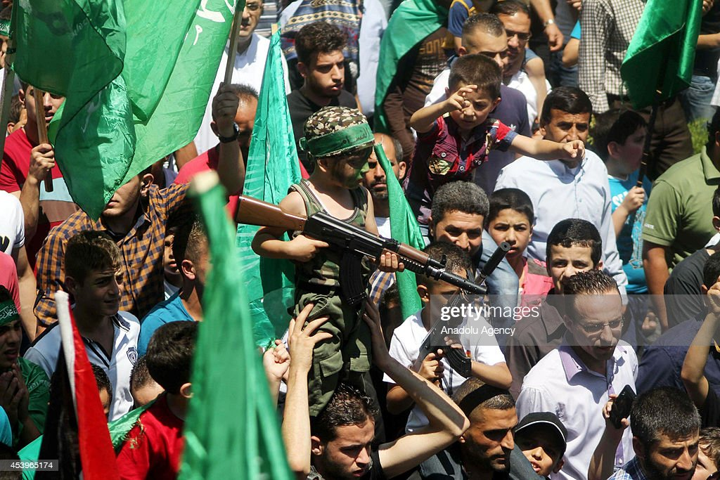 Palestinian kids hold toy rifles and as other people holding Hamas flags during solidarity demonstration staged for people living in Gaza after Friday Prayer in Hebron, West Bank on August 22, 2014.