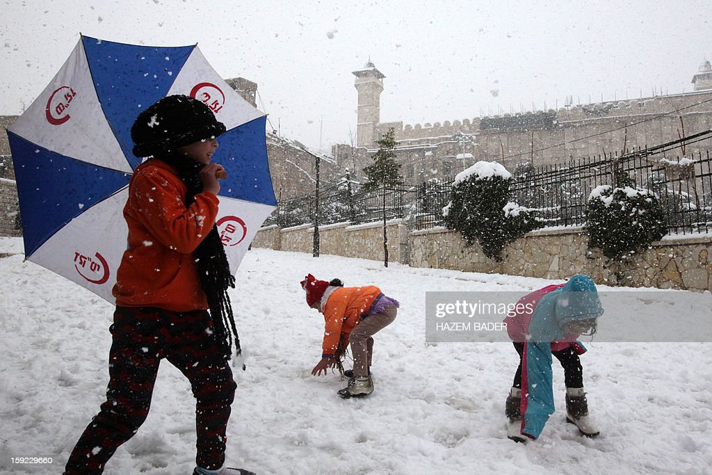 Palestinian kids play with the snow in front of the Ibrahimi Mosque or the Tomb of the Patriarchs on January 10, 2013 in the West Bank city of Hebron. As temperatures plummeted, the bitter winds and rain that have battered the Middle East since Sunday turned into snow, blanketing Jerusalem in white and closing schools and businesses, as much of the transport infrastructure ground to a halt.